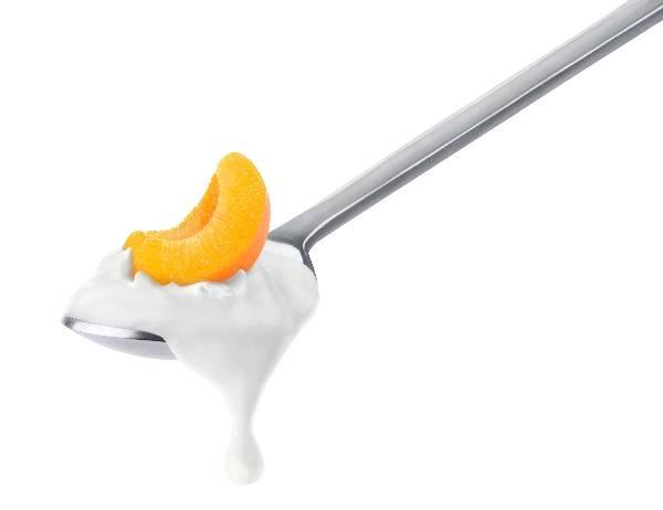 Фото - персик на ложке в сливках на белом фоне