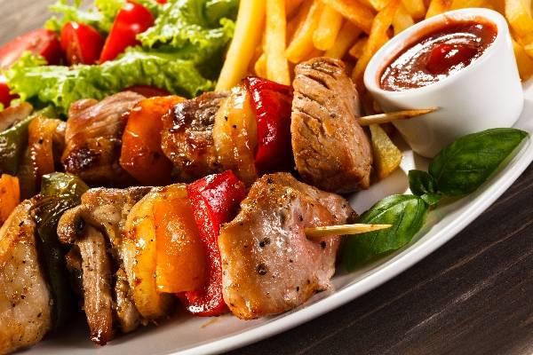 Шашлык на фоне соусов и овощей и картошки фри