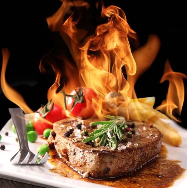 Стейк - гриль с овощами на огненном фоне