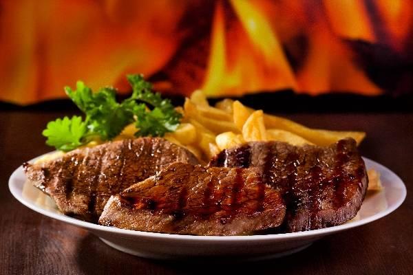 Стейк - гриль с овощами и картошкой фри, на огненном фоне